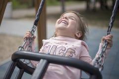 Απόλαυση ενός μικρού κοριτσιού από την οδήγηση σε μια ταλάντευση στοκ εικόνες