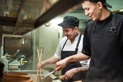 απόλαυση της εργασίας Δύο χαμογελώντας νέοι βοηθοί αρχιμαγείρων εργάζονται σε μια κουζίνα εστιατορίων στοκ εικόνες