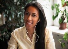 απόλαυση της μουσικής Ελκυστική νέα αφρικανική γυναίκα που φορά το ακουστικό Στοκ φωτογραφία με δικαίωμα ελεύθερης χρήσης