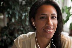 απόλαυση της μουσικής Ελκυστική νέα αφρικανική γυναίκα που φορά το ακουστικό Στοκ Εικόνες