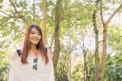 απόλαυση της φύσης Η νέα ασιατική γυναίκα οπλίζει αυξημένος απολαμβάνοντας το καθαρό αέρα στο πράσινο δάσος στοκ φωτογραφία