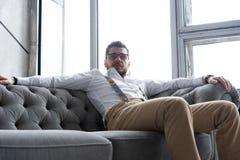Απόλαυση του ελεύθερου χρόνου Στοχαστικός νεαρός άνδρας στο πλήρες κοστούμι που κοιτάζει μακριά καθμένος στον καναπέ στο σπίτι στοκ εικόνες με δικαίωμα ελεύθερης χρήσης