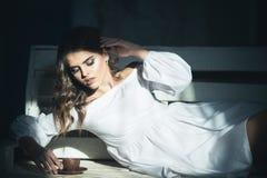 Απόλαυση του καφέ προκλητική γυναίκα που απολαμβάνει τον καφέ στο σπίτι πασπαλίζοντας στοκ εικόνα
