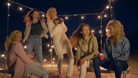 Απόλαυση του κόμματος παραλιών, ευτυχείς φίλες που χορεύει στην άμμο στις λάμπες φωτός απόθεμα βίντεο