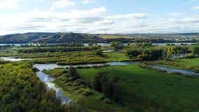 Απόμακρος πύργος ενάντια στον ποταμό που ρέει μεταξύ των πράσινων εγκαταστάσεων φιλμ μικρού μήκους
