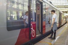 Απόμακρο σχέδιο του νέου ελκυστικού ατόμου που εξετάζει το προσεγγισμένο τραίνο στο σταθμό μετρό στοκ εικόνα