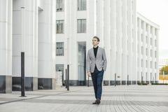 Απόμακρο σχέδιο του νέου επιχειρησιακού ατόμου που πηγαίνει δίπλα στο σύγχρονο εμπορικό κέντρο στοκ εικόνα