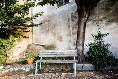 απόμερος ξύλινος πάγκος κάτω από το δέντρο παραδοσιακή γωνία του ιταλικού β στοκ εικόνα