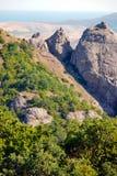 Απότομα δύσκολα βουνά, που κατεβαίνουν σε μια πράσινη κοιλάδα στα πλαίσια των ευγενών λόφων Στοκ εικόνες με δικαίωμα ελεύθερης χρήσης