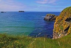 Απότομοι βράχοι κατά μήκος της ιρλανδικής ακτής δίπλα στο μικροσκοπικό νησί carrick-α Στοκ Εικόνες