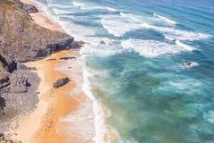 Απότομοι βράχοι, παραλία και κύματα σε Arrifana Στοκ Εικόνες