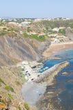 Απότομοι βράχοι, παραλία και σπίτια σε Arrifana Στοκ Φωτογραφίες