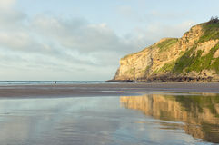 Απότομοι βράχοι που απεικονίζονται χρυσοί στο νερό στην παραλία στοκ εικόνες