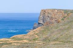 Απότομοι βράχοι, ωκεανός, βουνά και βλάστηση σε Arrifana Στοκ φωτογραφία με δικαίωμα ελεύθερης χρήσης