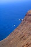 Απότομος βράχος, ωκεανός και βάρκα Στοκ Φωτογραφίες