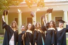 Απόφοιτοι φοιτητές που φορούν το καπέλο και την εσθήτα βαθμολόγησης Στοκ Φωτογραφίες