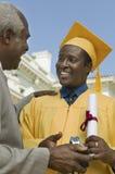 Απόφοιτος φοιτητής που λαμβάνει το δώρο από τον πατέρα Στοκ Εικόνα