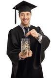 Απόφοιτος φοιτητής που βάζει ένα νόμισμα σε ένα βάζο Στοκ Εικόνες