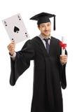Απόφοιτος φοιτητής που κρατά έναν άσσο της κάρτας και του διπλώματος φτυαριών Στοκ Εικόνες