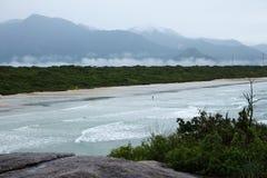Απόψεις παραλιών της ηπειρωτικής χώρας με τα κύματα, το δάσος, τα σύννεφα και τα βουνά στοκ φωτογραφία