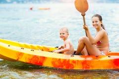 Απόλαυση παιδιών που κωπηλατεί στο καγιάκ στο θαλάσσιο νερό Στοκ εικόνες με δικαίωμα ελεύθερης χρήσης