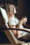 απόλαυση του βασικού χρόνου Κλείστε επάνω τη χαλάρωση γυναικών πορτρέτου στην άνετη σύγχρονη καρέκλα κοντά στην κούπα εκμετάλλευσ Στοκ εικόνα με δικαίωμα ελεύθερης χρήσης