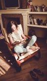 απόλαυση του βασικού χρόνου Χαλάρωση γυναικών στο άνετο σύγχρονο βιβλίο εγγράφου ανάγνωσης καρεκλών Φυσικό φως άνετο σπίτι Απολαύ Στοκ Φωτογραφίες