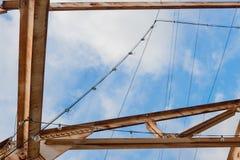 Από πάνω οξυδωμένες ζευκτόντα χάλυβα και σειρές του φωτός πριν από έναν μπλε ουρανό με τα σύννεφα Στοκ Εικόνες