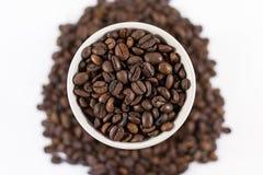 Από πάνω ψημένα φασόλια καφέ σε ένα φλυτζάνι στοκ φωτογραφία