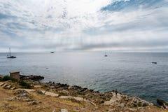 Από την αδριατική θάλασσα με τις βάρκες και τις ακτίνες στον ουρανό Δύσκολη παραλία με τους ανθρώπους Στοκ φωτογραφίες με δικαίωμα ελεύθερης χρήσης