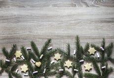 Από το κατώτατο σημείο σε έναν ξύλινο πίνακα είναι κομψά κλάδοι και marshmallows, μπισκότα πιπεροριζών υπό μορφή αστερίσκων και μ Στοκ Φωτογραφία