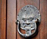 Από το Μπαλί δαίμονας ρόπτρων πορτών χαλκού στο ξύλινο υπόβαθρο Στοκ Φωτογραφίες