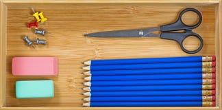 Απλές προμήθειες γραφείων μέσα του ξύλινου συρταριού γραφείων Στοκ Εικόνες