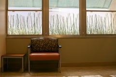 Απλό δωμάτιο με την ευρεία καρέκλα και το δευτερεύοντα πίνακα Στοκ φωτογραφία με δικαίωμα ελεύθερης χρήσης