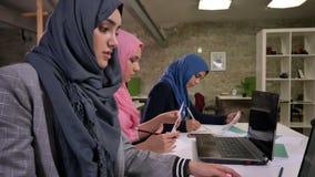 Αραβικά θηλυκά hijab Thre τα συμπαθητικά κάθονται στον κοινό υπολογιστή γραφείου στη γραμμή και εργάζονται κοντά στο lap-top στο  απόθεμα βίντεο