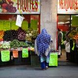 Αραβική γυναίκα με το πέπλο djellaba που αγοράζει μέσα ένα κατάστημα φρούτων στοκ φωτογραφία