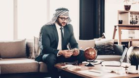 Αραβική συνεδρίαση στον καναπέ και τα μετρώντας χρήματα στοκ εικόνα