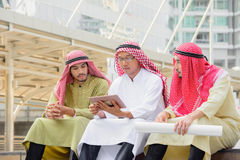 Αραβικοί επιχειρηματίες που κάθονται και που διοργανώνουν τις διαβουλεύσεις με τη χρησιμοποίηση της ταμπλέτας Στοκ φωτογραφίες με δικαίωμα ελεύθερης χρήσης
