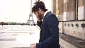 Αραβικός επιχειρηματίας που υποστηρίζει με το συνεργάτη από το smartphone κοντά στον πύργο του Άιφελ απόθεμα βίντεο