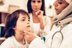 Αραβικός θηλυκός γιατρός που εξετάζει λίγο το αγόρι στοκ εικόνες