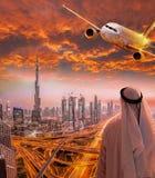 Αραβικό άτομο με το αεροπλάνο που πετά πέρα από το Ντουμπάι ενάντια στο ζωηρόχρωμο ηλιοβασίλεμα στα Ηνωμένα Αραβικά Εμιράτα Στοκ φωτογραφία με δικαίωμα ελεύθερης χρήσης