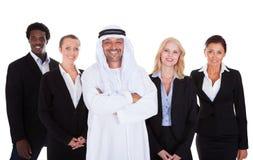 Αραβικό άτομο που στέκεται με Businesspeople στοκ εικόνα