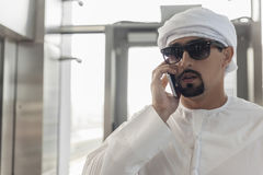 Αραβικό αρσενικό που χρησιμοποιεί το έξυπνο τηλέφωνο στο σταθμό μετρό Στοκ Εικόνες