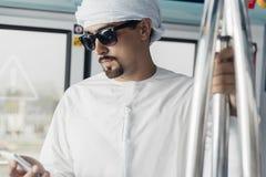 Αραβικό αρσενικό που χρησιμοποιεί το έξυπνο τηλέφωνο στο τραίνο μετρό Στοκ Εικόνα