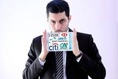 Αραβικό επιχειρησιακό άτομο με τα διάσημα λογότυπα τραπεζών Στοκ Φωτογραφίες