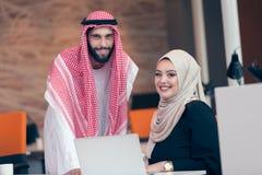 Αραβικό επιχειρησιακό ζεύγος που εργάζεται μαζί στο πρόγραμμα στο σύγχρονο γραφείο ξεκινήματος Στοκ Εικόνες