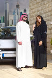 Αραβικό ζεύγος ενάντια στην τοποθέτηση αυτοκινήτων τους στο σπίτι με τη εικονική παράσταση πόλης πίσω Στοκ φωτογραφία με δικαίωμα ελεύθερης χρήσης