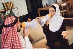 Αραβικό ζεύγος που κραυγάζει το ένα στο άλλο megaphone Στοκ Φωτογραφίες