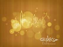 Αραβικό ισλαμικό καλλιγραφικό κείμενο Eid Μουμπάρακ στο καφετί υπόβαθρο. Στοκ Εικόνες