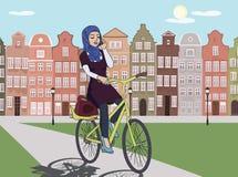 Αραβικό οδηγώντας ποδήλατο κοριτσιών στο τοπίο πόλεων της Ευρώπης Στοκ Εικόνες